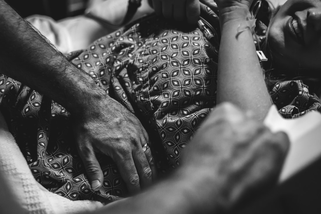 Black and White photo of dad rubbing mom's belly during birth lowcountry birth photographer