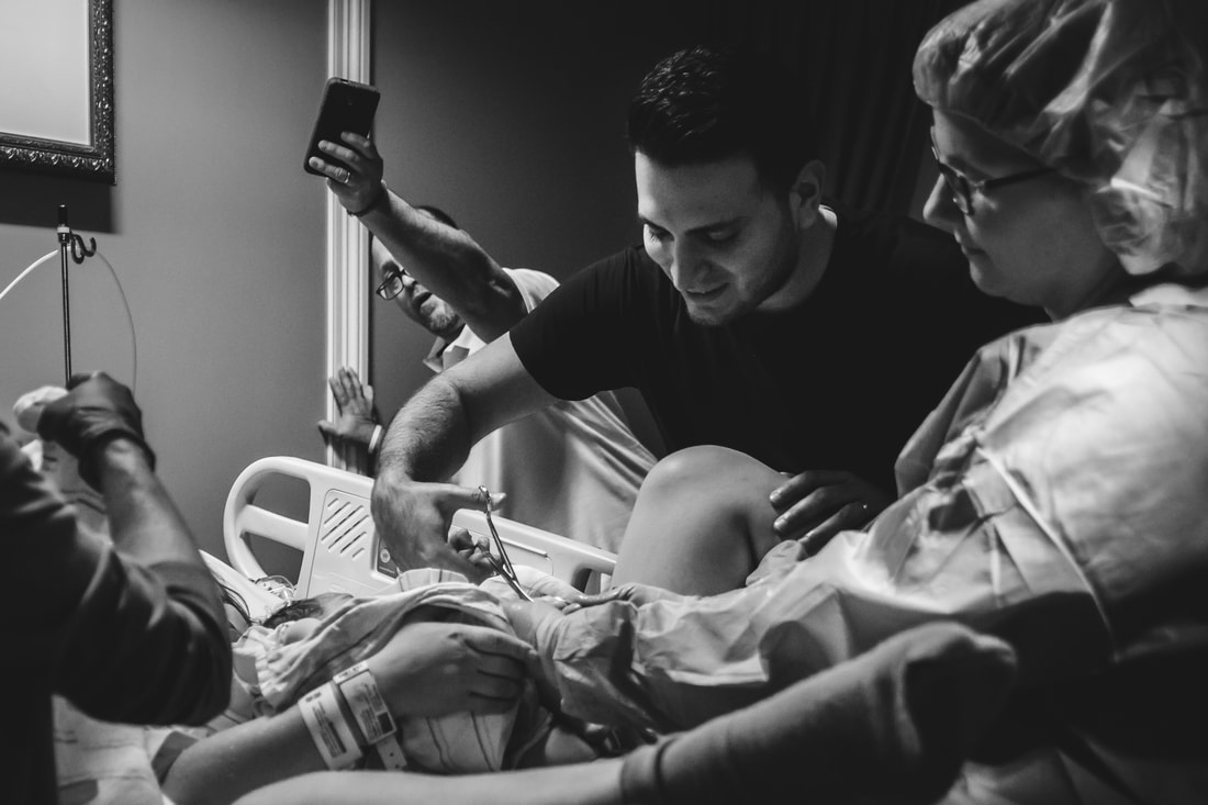 Picture of dad cutting umbilical cord after birth