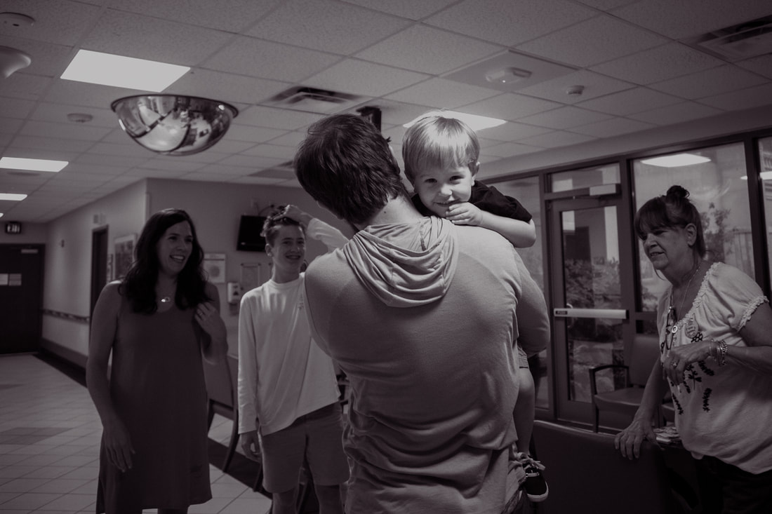 black and white photo of a dad picking up his son to go meet their new baby during a lowcountry birth story
