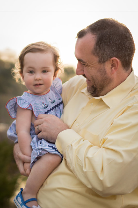 Photo of dad tickling his toddler daughter in Charleston, SC at a sunrise family session