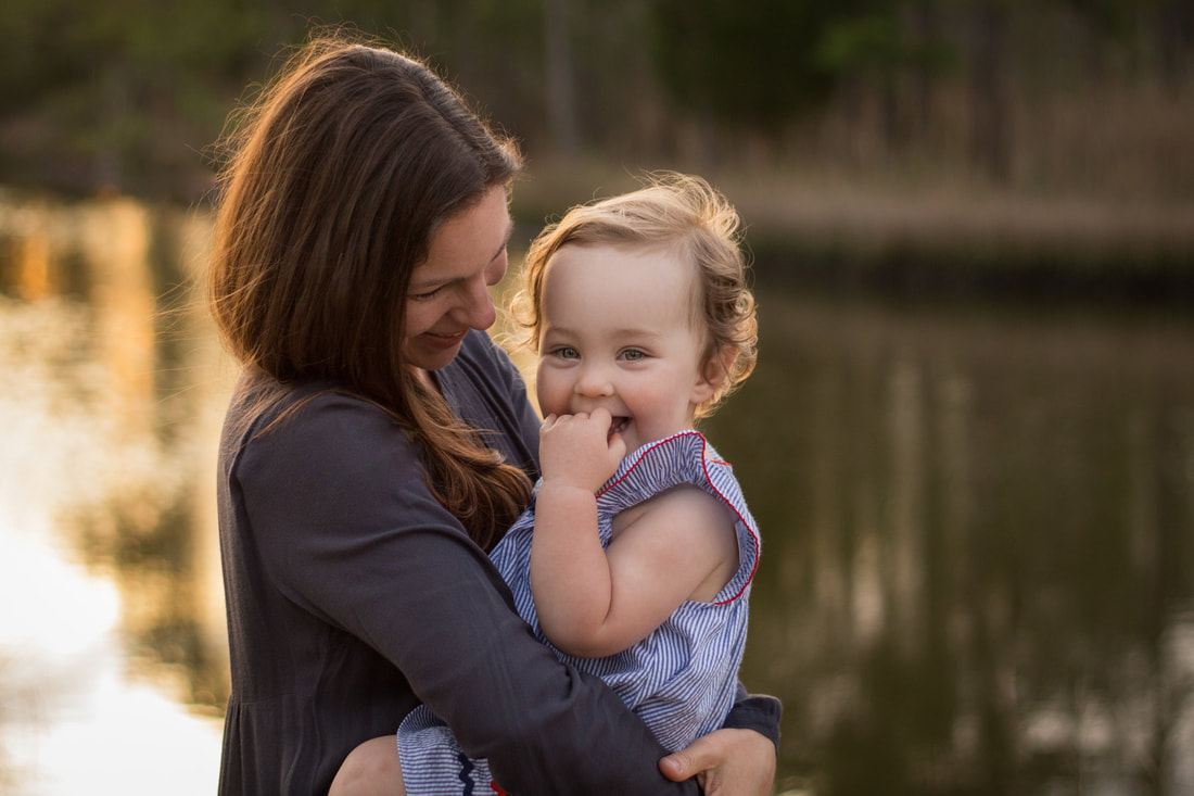 Photo of a mom with her toddler daughter by the water in Charleston, SC during a sunrise family portrait session