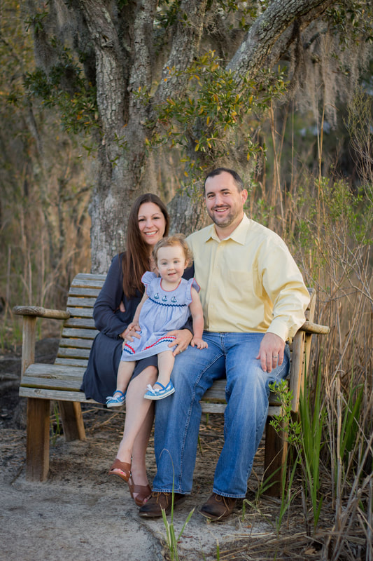 A family portrait of dad, mom, and toddler daughter sitting on a bench at sunrise in Charleston, SC