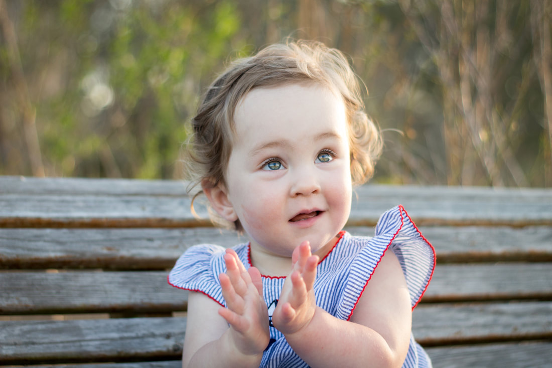 Photo of a toddler girl clapping hands during a lifestyle family photo session in Charleston, SC