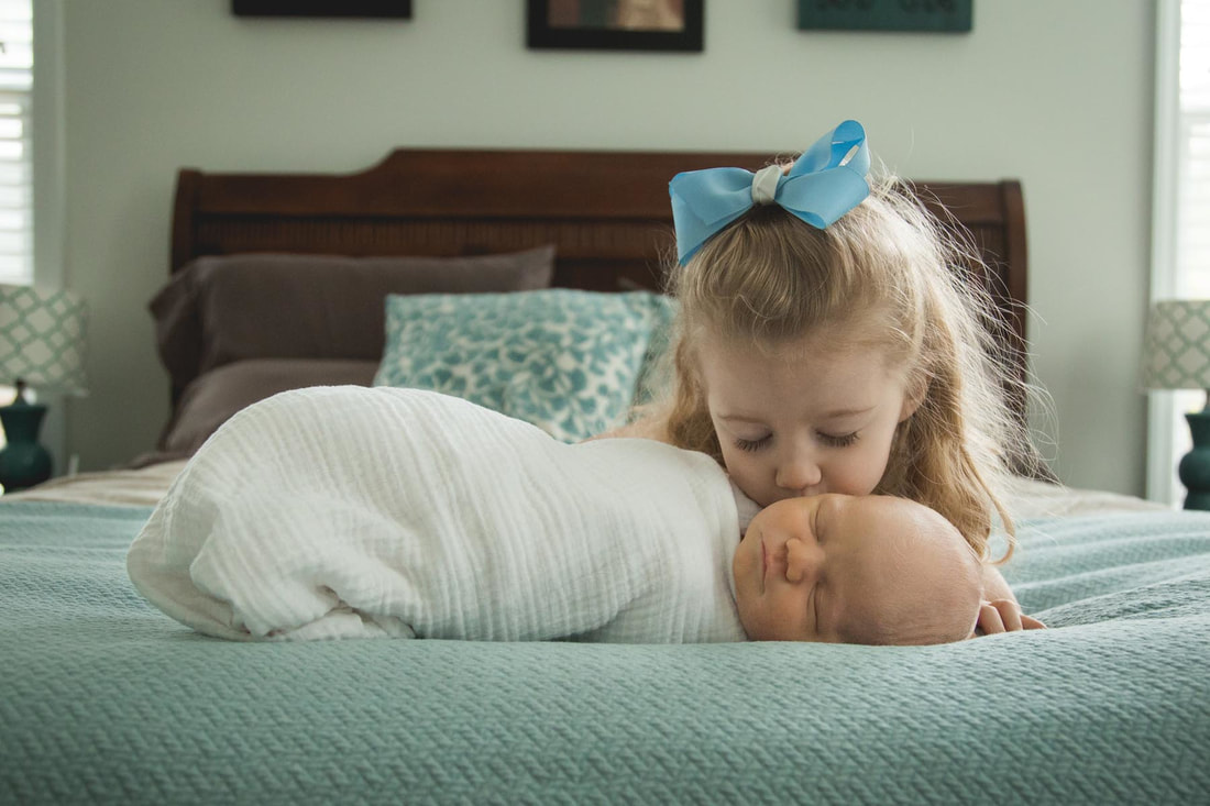Big sister kissing her sleeping newborn brother during a lifestyle photography session in mt pleasant sc