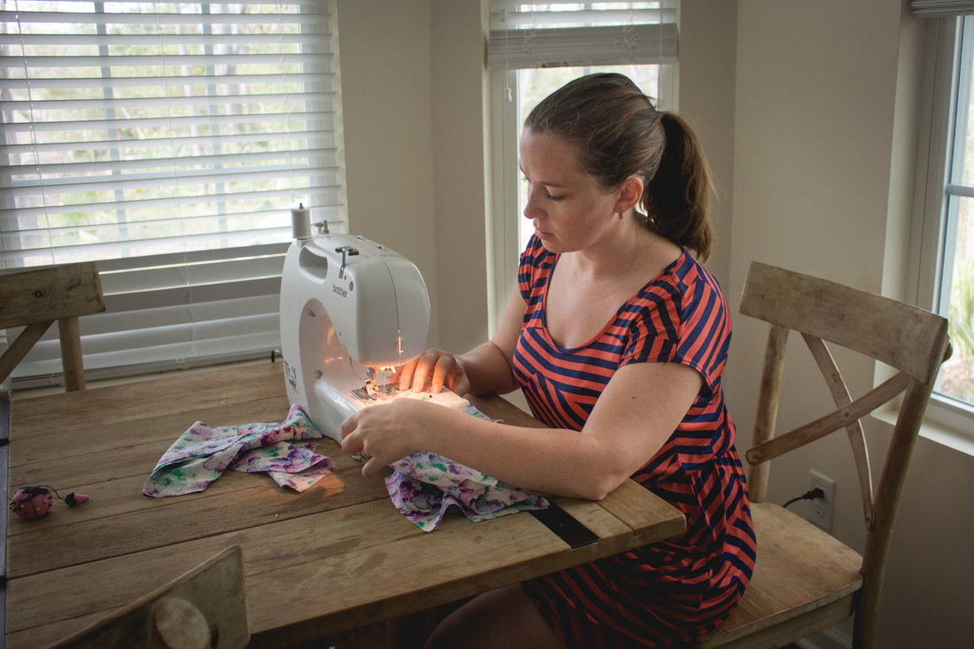 Lifestyle photograph of a mother sitting at a sewing machine making a dress for her daughter